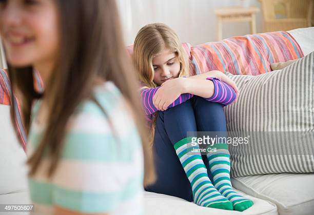 Girl sitting apart from friends, sad