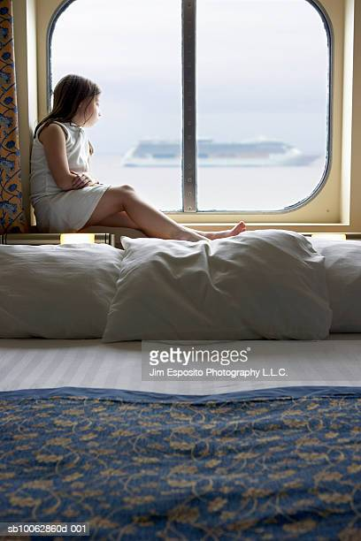 Girl (6-7) sitting at cabin window on cruise ship