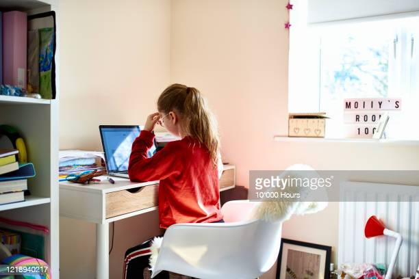 girl sitting at desk doing homework during lockdown - primary school child stock pictures, royalty-free photos & images