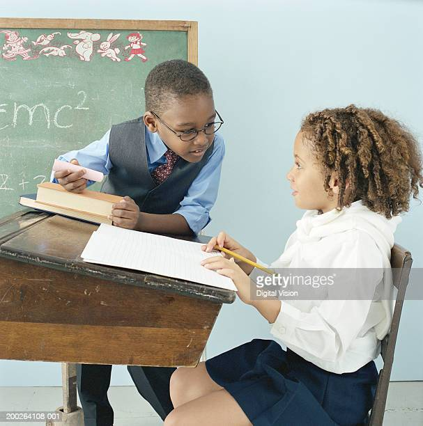girl (4-6) sitting at desk in classroom looking at boy (5-7) - teacher bending over stock photos and pictures