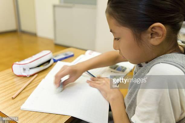 Girl sitting at desk in classroom, using eraser, blurred motion