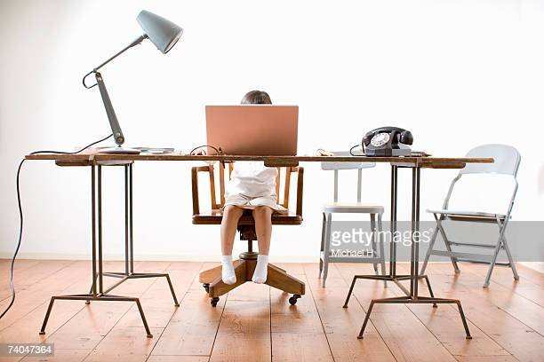 Girl (6-7) sitting at desk, using laptop