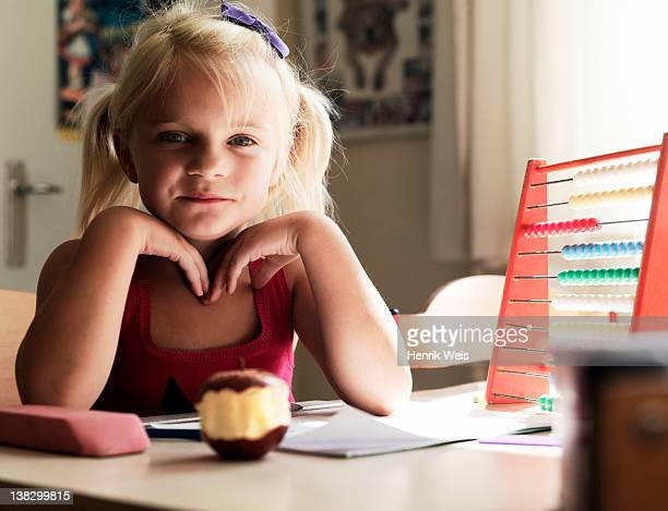 Girl sitting at desk with apple