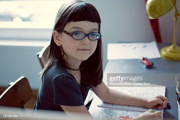 Girl sitting at desk with coloring book