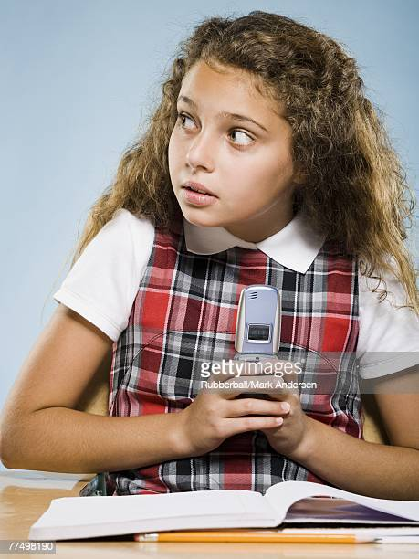 Girl sitting at desk with workbook hiding cell phone
