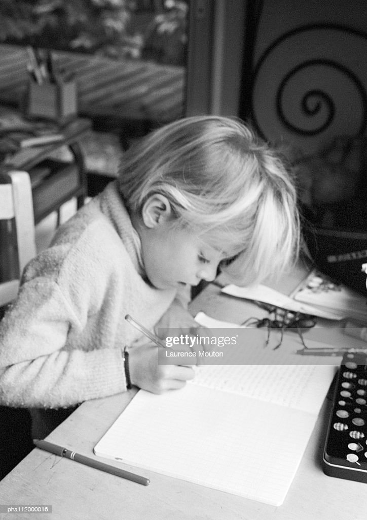 Girl sitting at desk, writing in notebook, b&w : Stockfoto