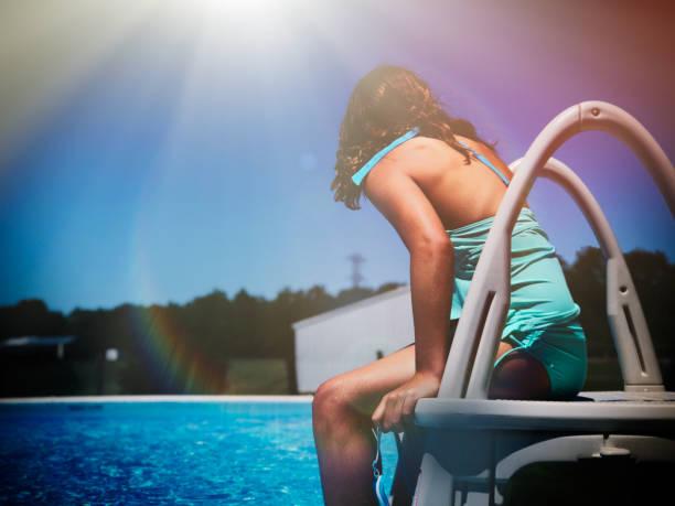 girl sitting at swimming pool's edge