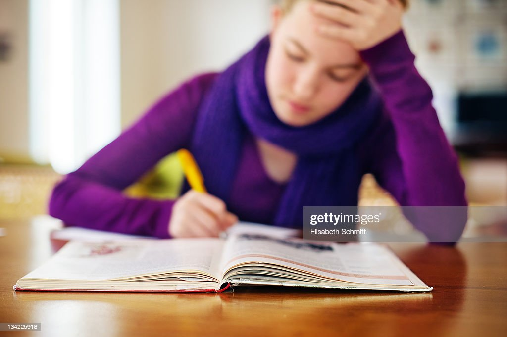 Girl sitting at table and doing her homework : Stock Photo