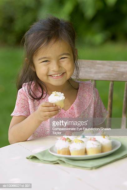 Girl (6-7) sitting at table outdoors, eating cupcakes, portrait