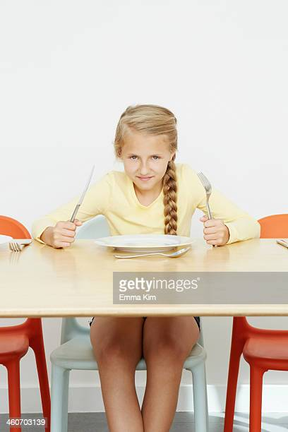 Girl sitting at table with empty plate holding cutlery