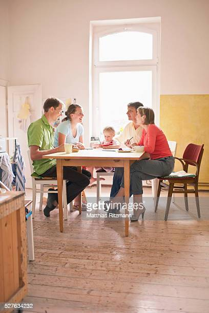 Girl (1-2) sitting at table with parents and grandparents