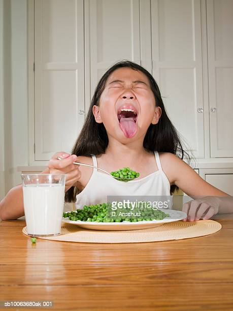 girl (8-9) sitting at table with plate of green peas, sticking out tongue - girls open mouth stock photos and pictures