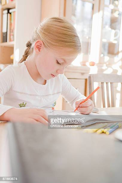 girl sitting at table writing - colouring book stock photos and pictures