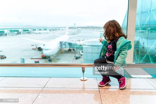 girl sitting at the airport in front of a plane, ready to travel - toddler at airport stock pictures, royalty-free photos & images