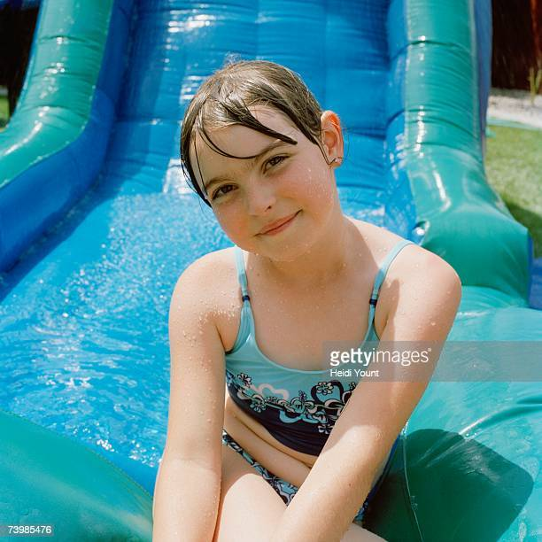 Girl sitting at the bottom of a water slide