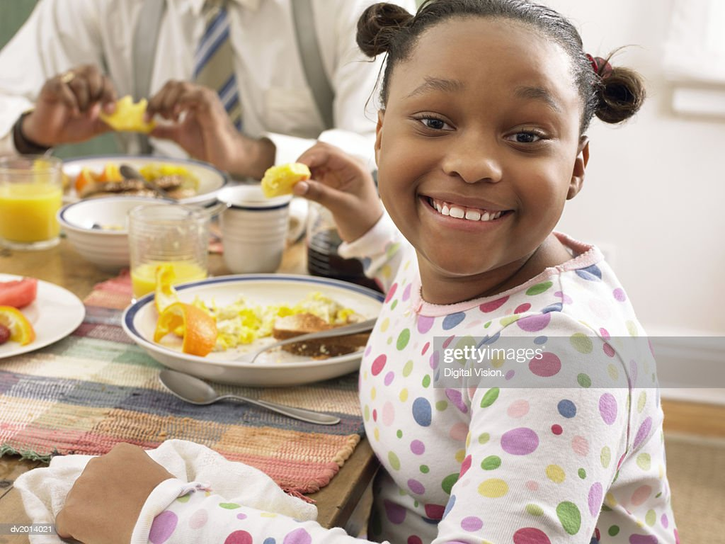 Girl Sitting at the Breakfast Table Eating Fruit : Stock Photo