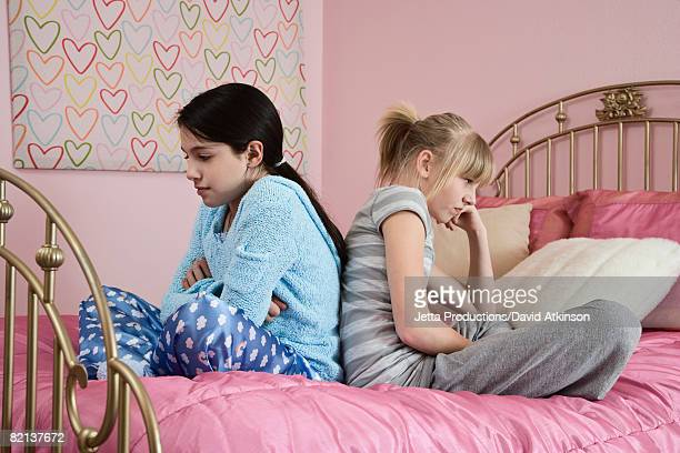 girl sitting back to back on bed - girl fight stock photos and pictures