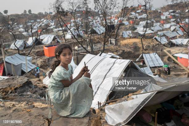 Girl sitting beside a temporary shelter set up for displaced Rohingya refugees days after a fire at a refugee camp in Ukhia, in the southeastern...