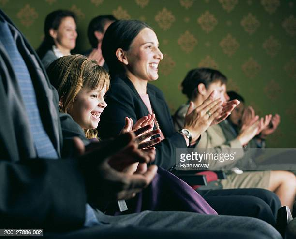 Girl (6-8) sitting between parents, applauding at theater