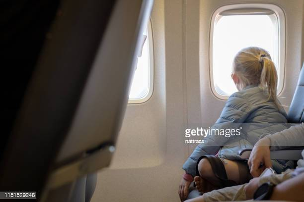 girl sitting by brother looking through window - parte mediana imagens e fotografias de stock