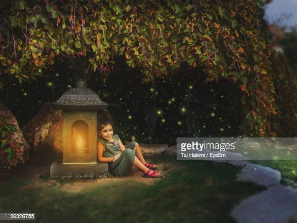 girl sitting by built structure against trees - hakimi stock photos and pictures