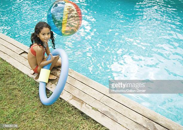 Girl sitting by edge of pool, holding floating ring