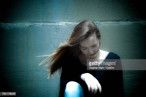 Girl Sitting By Wall