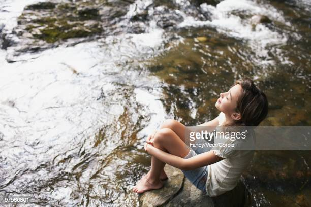 Girl sitting by water