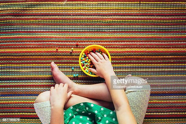 Girl sitting cross legged eating multi-colored snacks