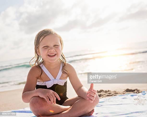 Girl (4-5) sitting cross- legged on beach