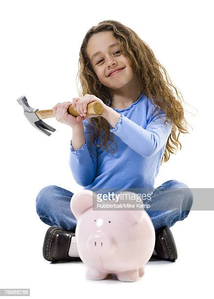 Girl sitting cross legged with hammer and piggy bank smiling