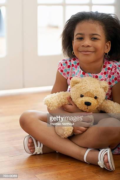 Girl (4-6) sitting cross-legged on floor holding teddy