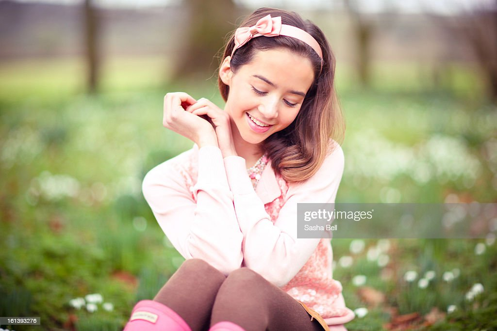 Girl Sitting Down in Snowdrop Woodland : Stock Photo