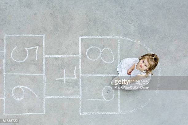 girl sitting down on hopscotch grid, looking up, overhead view - hopscotch stock pictures, royalty-free photos & images