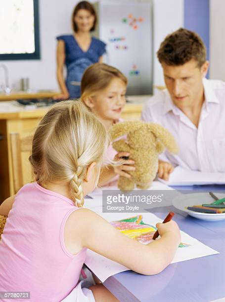Girl sitting holding a teddy bear with his father and sister