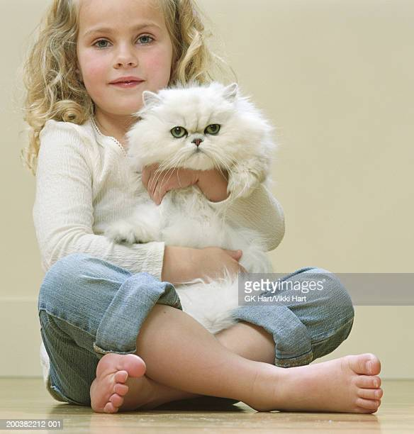 girl (4-6) sitting holding white persian cat, smiling, portrait - persian girl stock photos and pictures