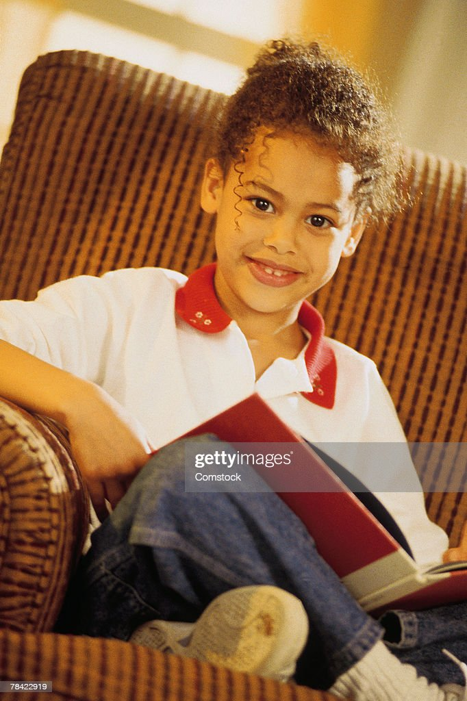 Girl sitting in a chair reading a book : Foto de stock