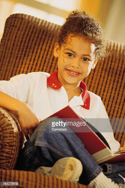 girl sitting in a chair reading a book - 1990 1999 - fotografias e filmes do acervo