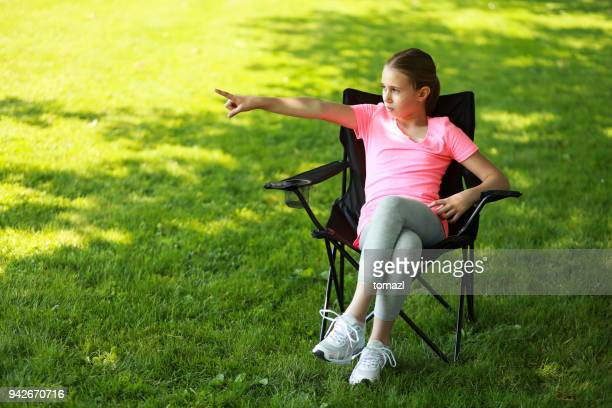 Girl sitting in a picnic chair and ordering people around