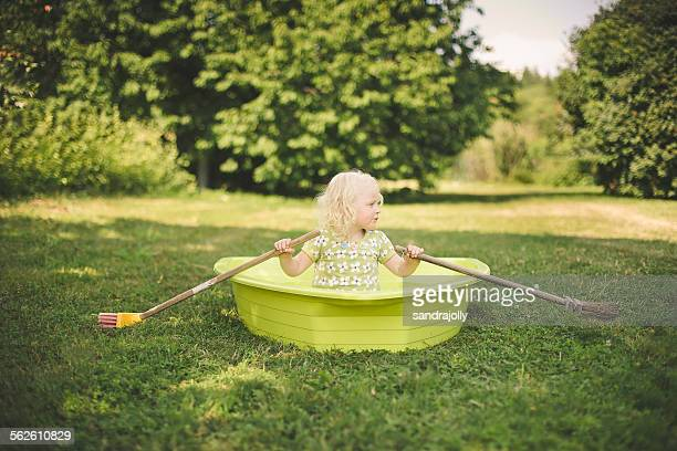 Girl sitting in a rowing boat in the garden