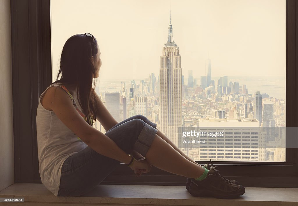 Girl Sitting In A Window Looking Views Of New York Stock