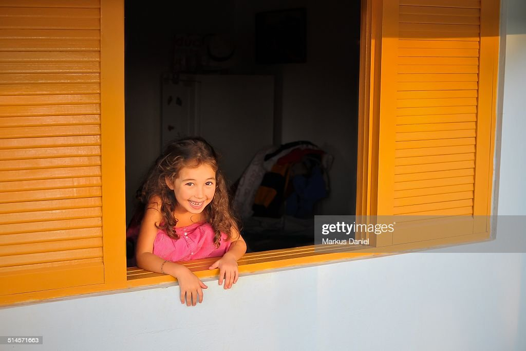 Girl sitting in a window : Stock Photo
