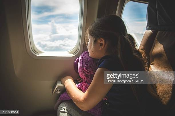 girl sitting in airplane looking out of window - aeroplane stock photos and pictures