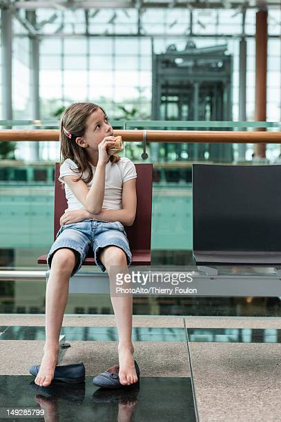 girl sitting in airport eating sandwich, portrait - kid in airport stock pictures, royalty-free photos & images
