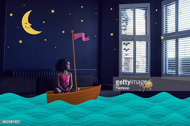 Girl sitting in an imaginary boat on the sea