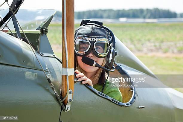girl sitting in an open cockpit biplane - doppeldecker flugzeug stock-fotos und bilder