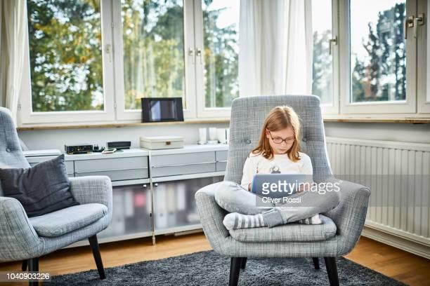 girl sitting in armchair using digital tablet at home - nur kinder stock-fotos und bilder