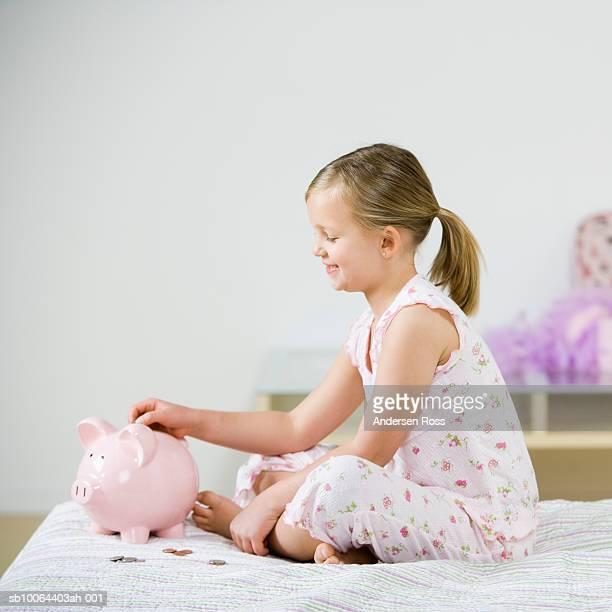 Girl (6-7) sitting in bed filling piggy bank