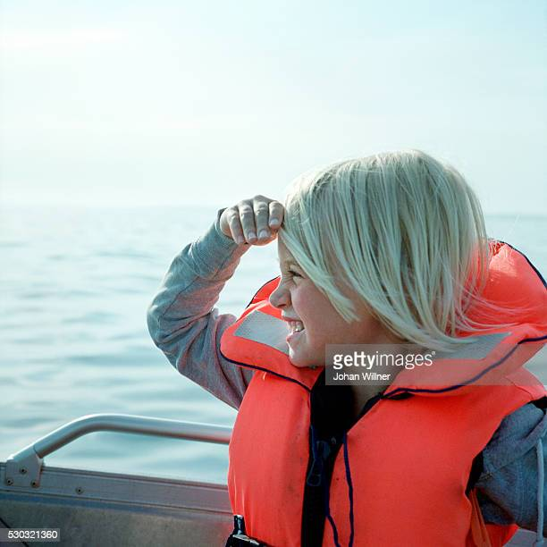 Girl sitting in boat and looking away