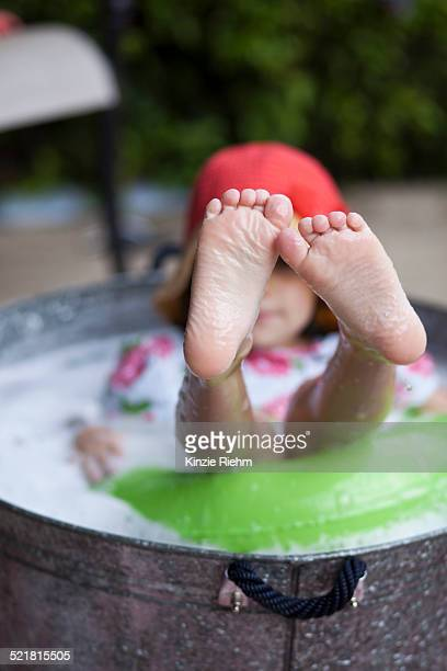 girl sitting in bubble bath in garden with feet sticking out - wet t shirt girls stock photos and pictures